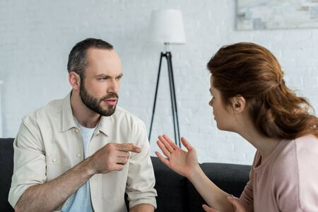 selective focus of handsome man pointing with finger at woman at home