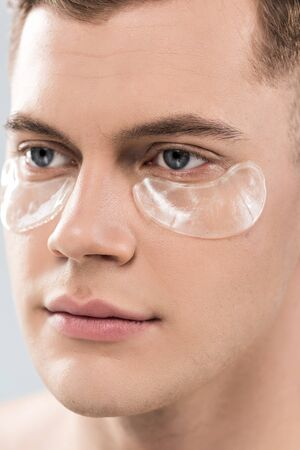 Portrait of handsome young man with eye patches looking away