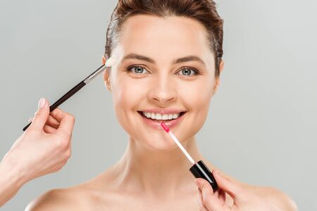 Cropped view of cosmetic artists holding lip gloss and cosmetic brush near happy naked woman isolated on grey background
