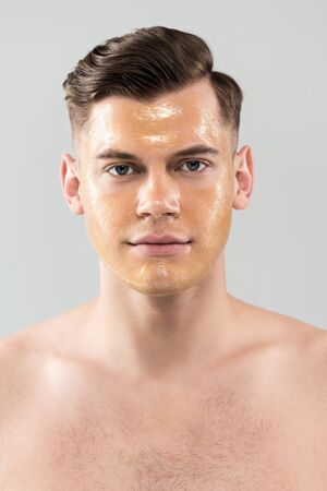 Front view of naked young man with facial mask isolated on grey background