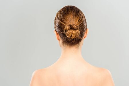Back view of naked woman standing isolated on grey background