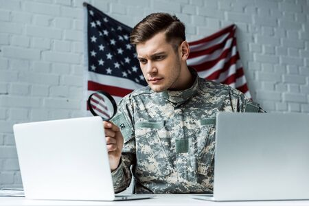 handsome soldier holding magnifying glass near laptops