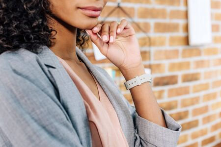 Cropped view of African American Casual businesswoman touching chin in loft office