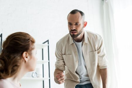 selective focus of angry man showing fist while looking at wife at home