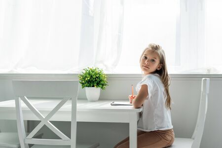 Cute kid sitting and holding pencil near notebook at home