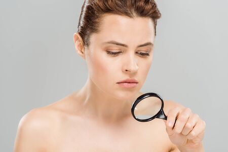 upset and naked woman holding magnifying glass isolated on grey
