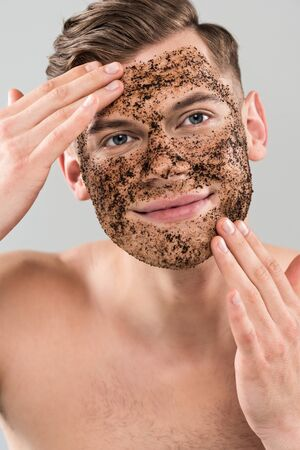 Front view of smiling young man applying scrub isolated on grey background
