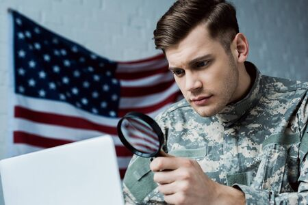 low angle view of young soldier in uniform holding magnifying glass near laptop in office