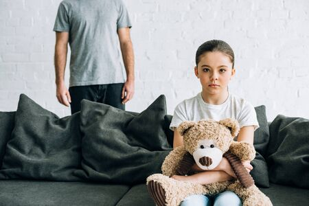 partial view of father and sad daughter with teddy bear sitting on sofa