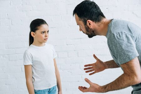 bearded angry father scolding upset daughter at home Stock Photo