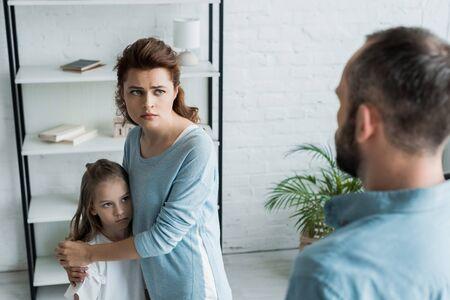 Enfoque selectivo de madre asustada abrazando a su hija y mirando al marido