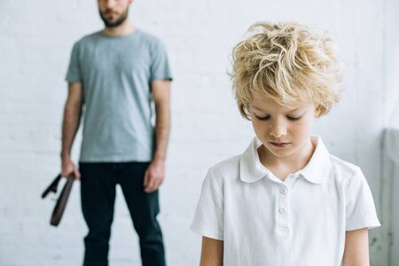 cropped view of father with belt and upset son at home