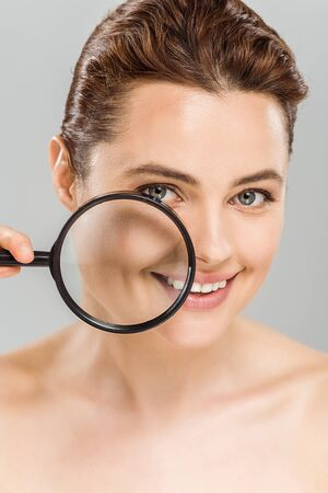 happy naked woman holding magnifying glass near face isolated on grey