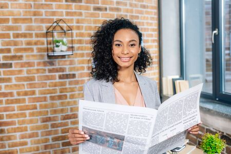 Beautiful smiling African American Casual businesswoman holding Business newspaper in loft office Stockfoto