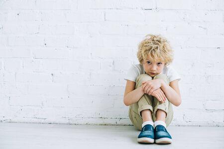 Upset preteen boy sitting on floor at home