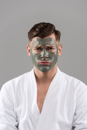 Front view of sad young man in bathrobe with clay mask isolated on grey background Stockfoto