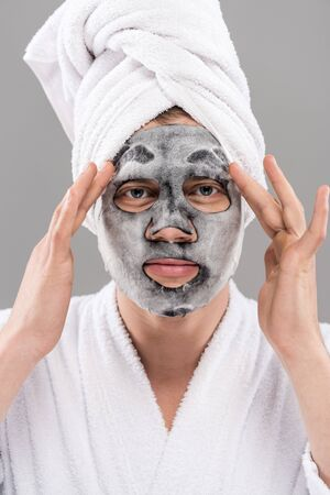 Front view of man in bathrobe with facial mask isolated on grey background
