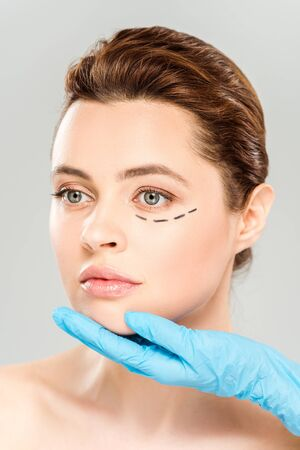 Cropped view of plastic surgeon touching face of pretty woman with marked face isolated on grey background 스톡 콘텐츠