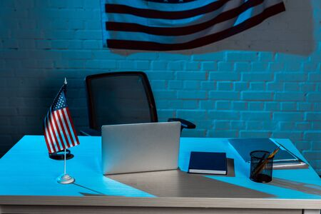 laptop near stationery near american flag in modern office 版權商用圖片
