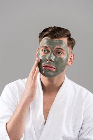 Worried man with clay mask in white bathrobe touching face isolated on grey background 免版税图像