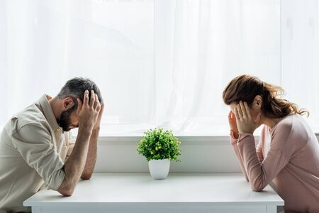 upset man and woman sitting at home after quarrel Stock Photo