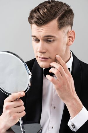 Young man in formal wear looking in mirror and touching face isolated on grey background