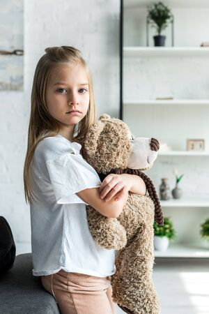 Cute kid looking at camera and holding teddy bear at home