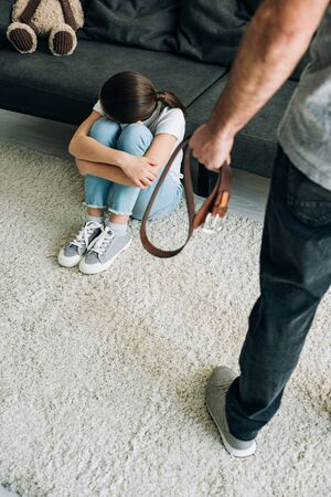 overhead view of father with belt and daughter sitting on floor