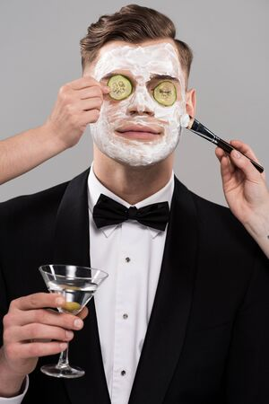 Cropped view of cosmetologists applying cucumber mask and man in formal wear holding glass of martini 스톡 콘텐츠