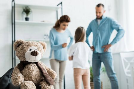 selective focus of teddy bear near quarreling family at home