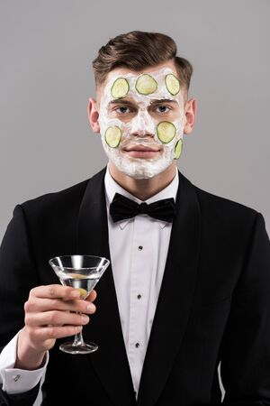 Young man in formal wear with cucumber facial mask holding glass of cocktail isolated on grey background