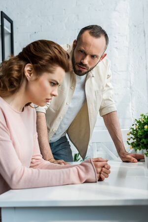 selective focus of man looking at offended brunette woman Stock Photo