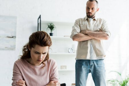 selective focus of offended woman near bearded man with crossed arms