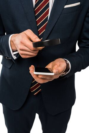 cropped view of businessman in suit holding magnifying glass near smartphone isolated on white Фото со стока