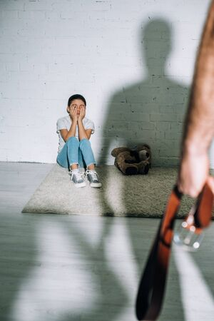 cropped view of father holding belt and scared daughter sitting on carpet near his silhouette Stock Photo