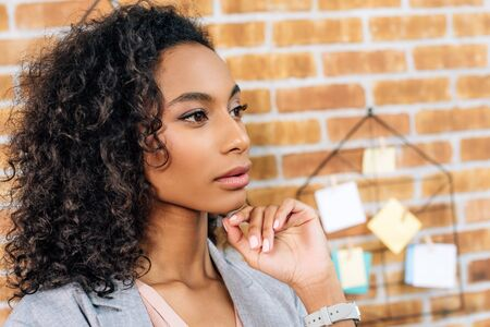 Thoughtful African American Casual businesswoman touching chin in loft office