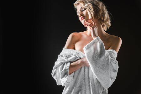 beautiful sexy young woman in white bathrobe posing isolated on black with copy space