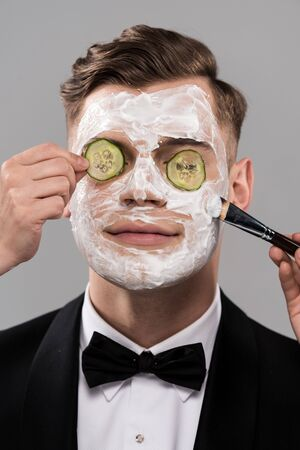 Partial view of cosmetologists applying cucumber mask and man in formal wear isolated on grey background