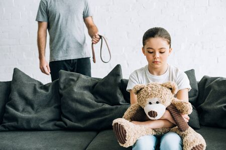 partial view of abusive father with belt and sad daughter with teddy bear sitting on sofa Stock Photo