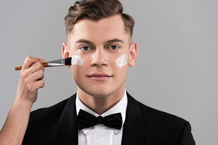 Cropped view of cosmetologist applying cream and man in formal wear isolated on grey background 스톡 콘텐츠
