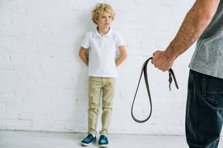 cropped view of father holding belt and son having conflict Stock Photo