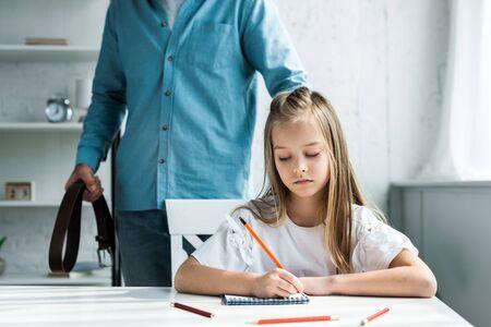 Vue recadrée du père tenant la ceinture et debout près d'un enfant mignon tenant un crayon près du cahier Banque d'images