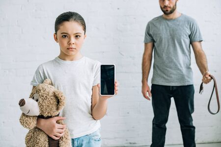 partial view of abusinve father and daughter with teddy bear showing smartphone with blank screen
