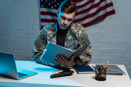 handsome military man holding folder while sitting in modern office