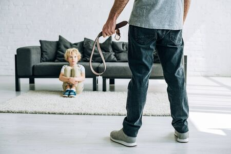 partial view of abusive father holding belt and sad son sitting on carpet Stock Photo