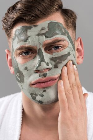 Displeased young man with clay mask touching face isolated on grey background Stockfoto