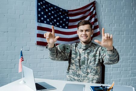 cheerful man in military uniform pointing with fingers and smiling near laptop