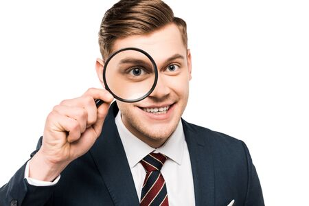 cheerful businessman holding magnifying glass near eye isolated on white