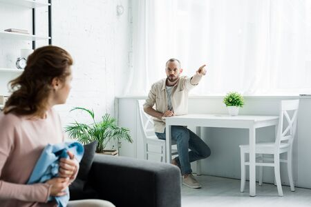 selective focus of upset bearded man pointing with finger while looking at woman