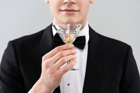 Cropped view of smiling man in formal wear holding glass of cocktail isolated on grey background 스톡 콘텐츠